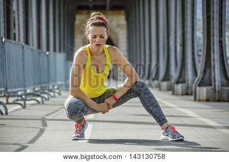 Healthy Woman Relaxing After Workout On Bridge In Paris