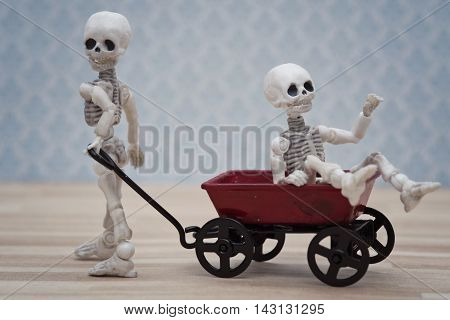 Skeleton kid pulling red toy wagon with his friend in it