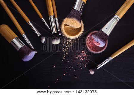 Make Up Brushes With Powder And Rouge On A Black Wooden Backgrou