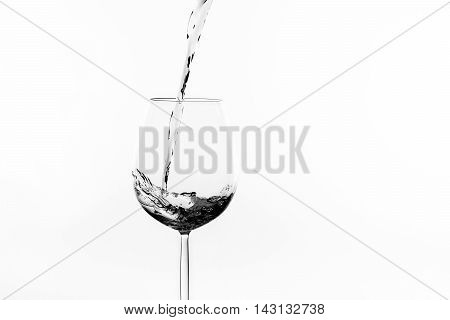 Red wine is pured into a wine glass and splashes in black and white
