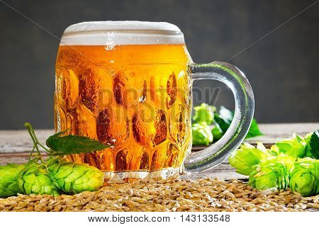 glass of beer with hop cones on the wooden desk