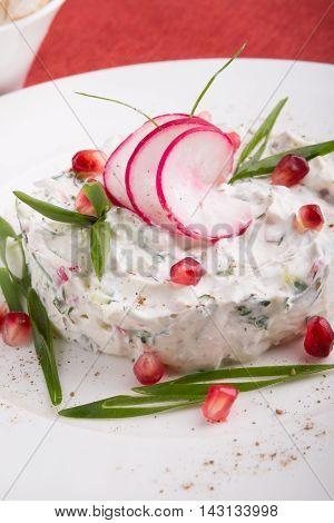 White uzbek salad snack with pomegranate and radish