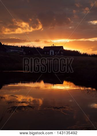 Mountain sunset with river reflection and dark silhouette of forest and rooftop, Jizerka village, Jizera Mountains, Czech Republic