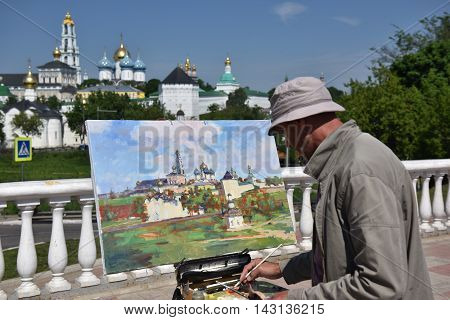 Sergiev Posad, Russia - may 28, 2016: A street painter draws a picture of the Cathedral of the Holy Trinity-St. Sergius Lavra. Sergiyev Posad is included into the Golden ring of Russia and is a pilgrimage center of the Christian world.