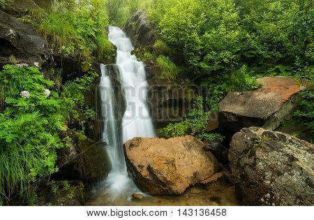 Waterfall in the canyon. Beautiful natural landscape in the summer time