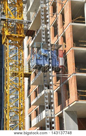 Building site with high-rise block under construction in an urban environment dominated by a large industrial crane silhouette. Building crane and building under construction