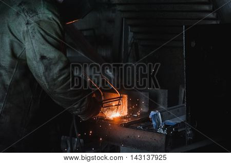 The job of a welder. A large concrete products plant and welding on it.
