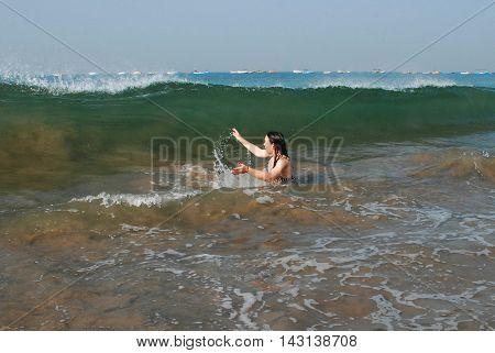 Beautiful girl in a sea is protecting by hands against a breaking wave