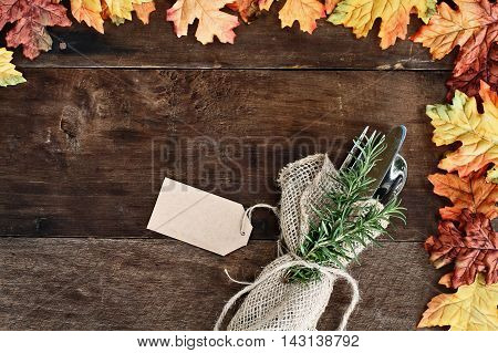 Silverware and burlap napkin with tag over rustic fall background of autumn leaves. Image shot from overhead.