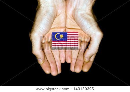 Flag Of Malaysia In Hands On Black Background