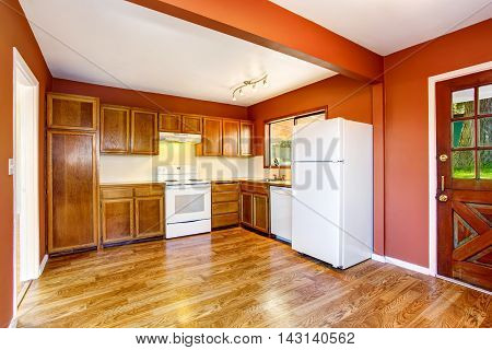 Kitchen Room With Woden Cabinets, Hardwood Floor And Red Walls.