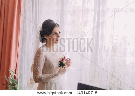 Close-up portrait of beautiful bride in wedding dress near window holding boutonniere.