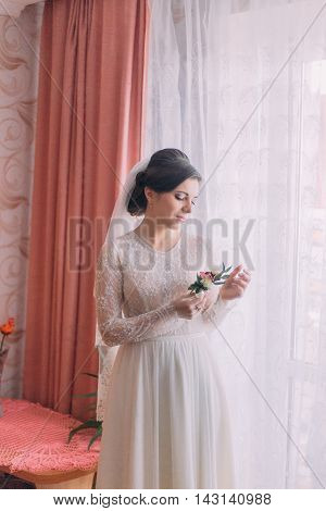 Portrait of beautiful bride in wedding gown near window holding boutonniere.