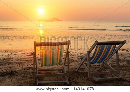 Pair of beach loungers on the sea sunset.