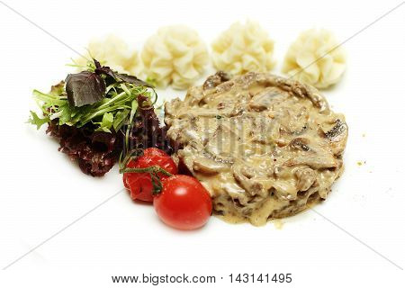 Roasted meat and garnish on white plate
