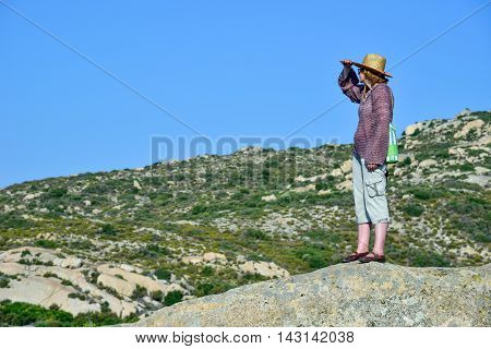 Woman standing on the rock of the mountain looking and enjoying the nature