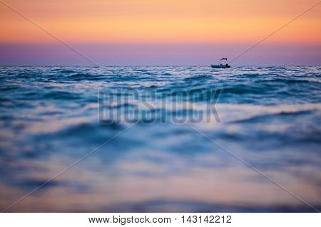 Boat On Waves At Sunset