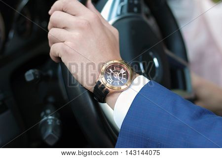 Businessman driving his car hand on the steering wheel. Hand with golden watch. Business concept.
