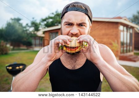 Young bearded hipster guy eating delicious burger outdoors