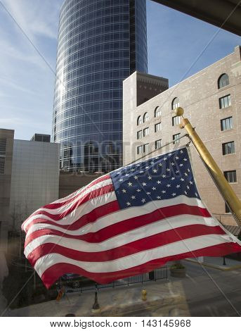U.S. flag in the wind skyscraper cityscape glass windows reflection