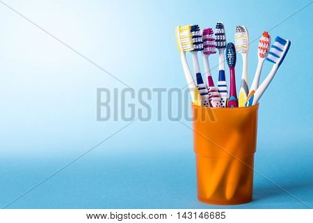 Various colorful toothbrushes in yellow cup on bright blue background with color gradient. The image has copy-space on the left side.
