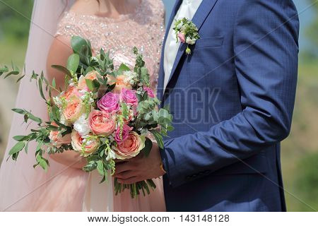 Beautiful bridal bouquet in hands of the bride. Wedding bouquet of peach roses by David Austin single-head pink rose aqua eucalyptus ruscus gypsophila