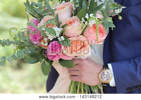 Beautiful bridal bouquet in hands of the groom. Wedding bouquet of peach roses by David Austin single-head pink rose aqua eucalyptus ruscus gypsophila