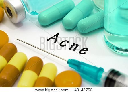 Acne - diagnosis written on a white piece of paper. Syringe and vaccine with drugs