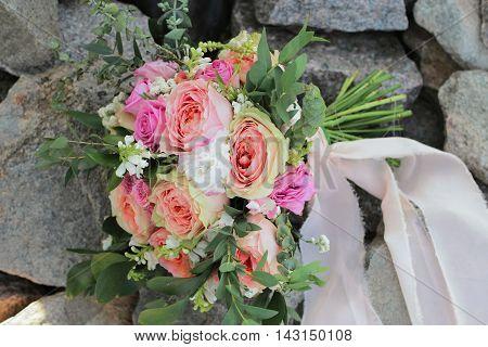 Bridal bouquet lying on the rocks. Wedding bouquet of peach roses, single-head pink rose aqua, eucalyptus ruscus, gypsophila