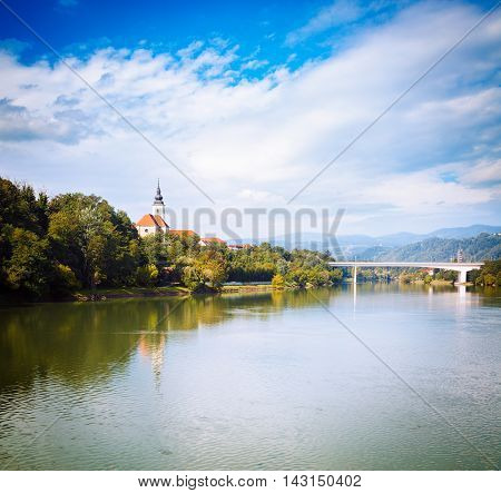 Old Church on River Bank on Mountains Background. Typical Landscape in Slovenia. St. Joseph Church in Maribor on Drava River. Popular Touristic Destination in Slovenia, Europe. Toned Photo.