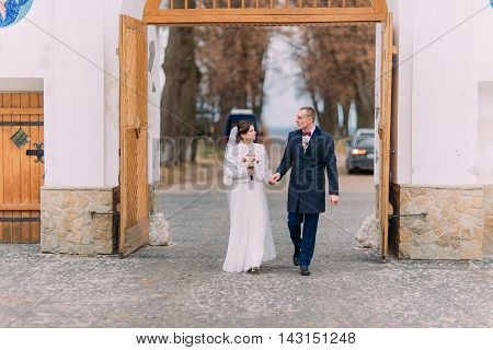 Newlywed pair walk through the gateway holding hands together.