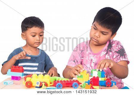 Two cute little asian boy play building brick
