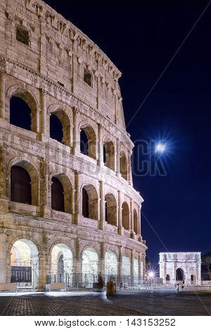 Roman Coliseum and Arch of Constantine illuminated by the full moon. Night photography