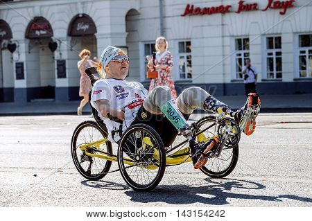 Ekaterinburg Russia - August 7 2016: male athlete with a disability on a wheelchair rides through city streets during Marathon Europe-Asia
