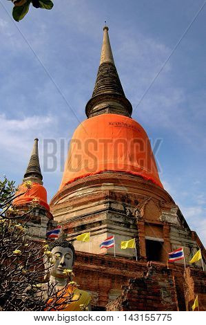 Ayutthaya Thailand - December 28 2005: Orange sashes cover the bell-shaped Chedis at Wat Yai Chai Mongkhon