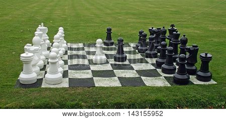 Outdoor large size chess set laid out on a grass lawn. Pieces appear to be in the correct places.