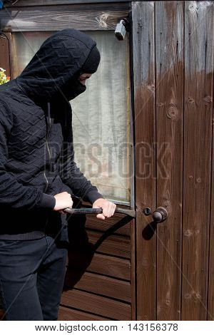 Burglar breaking and entering a garden shed