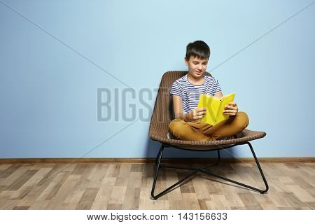 Cute boy reading book on blue wall background
