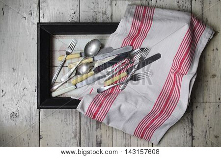 Vintage cutlery in a vintage box with kitchen towel.