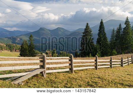 Wooden fence in a mountain village. Summer landscape with beautiful clouds and spruce forest on the slope. Sunny weather. Carpathians, Ukraine, Europe