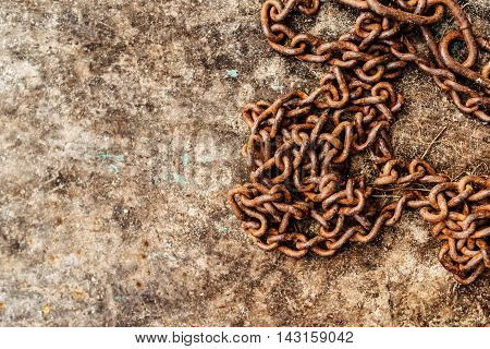 Rusty old chain on obsolete surface as copy space