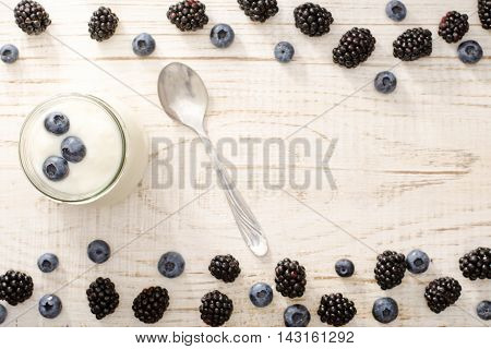 Jar of yogurt with blueberries teaspoon blackberries and blueberries on the edges