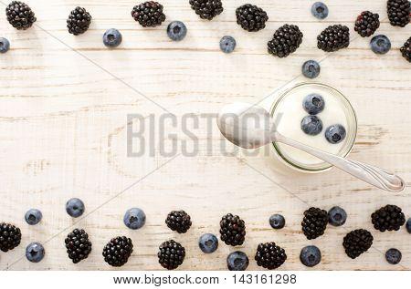 Yogurt with blueberries teaspoon blackberries and blueberries on the edges a top view