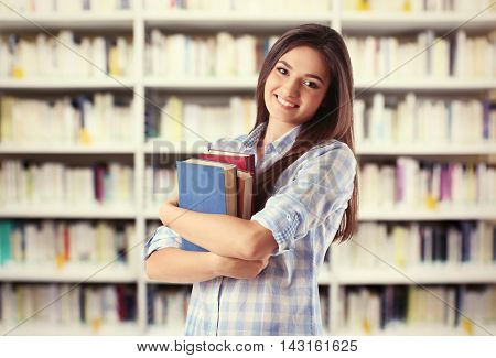 Beautiful young woman holding books on blurred book shelves background. Library concept.
