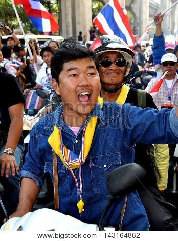 Bangkok Thailand - January 13 2014: Exuberant Thai man riding on a motorcycle during the anti-government Operation Shut Down Bangkok protests