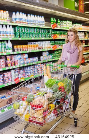 Young woman shopping and choosing goods in supermarket with trolley full of products