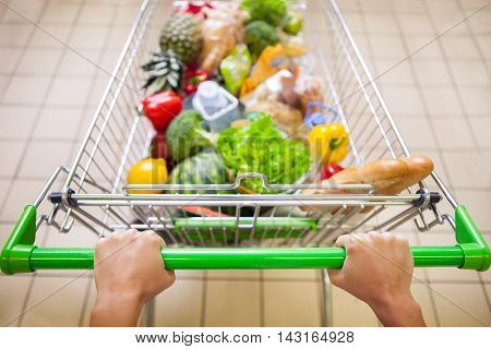 Man with trolley full of products in supermarket top view