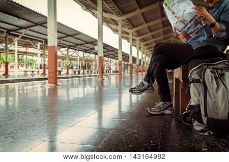 Young girl traveler sitting with backpack look searching location map at the train station Travel concept soft focus vintage tone