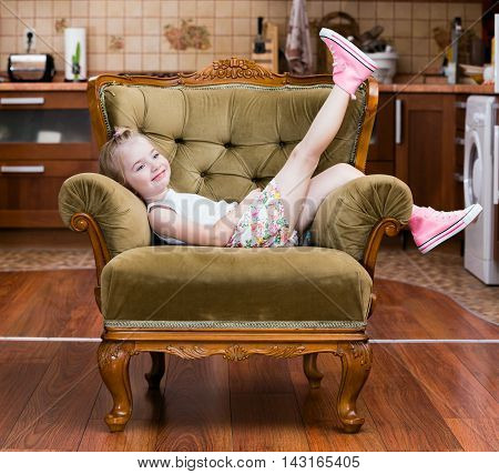Little girl shows pink sneakers on chair
