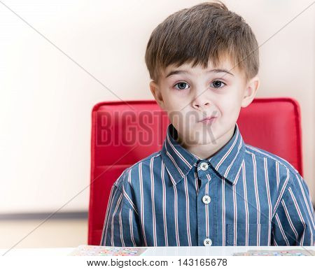 The puzzled little boy at the table in kitchen
